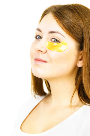Young woman applying golden collagen patches under eyes. Mask removing wrinkles and dark circles. Girl taking care of delicate skin around eye. Beauty treatment.