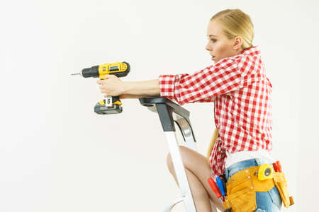 Young woman with checked shirt using drill for her work at home. Girl working at flat remodeling. Building, repair and renovation.