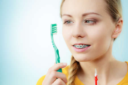 Dentist and orthodontist concept. Young woman with blue braces cleaning and brushing teeth using two different brushes, little interdental brush and manual toothbrush
