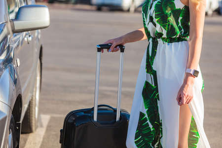 Fashionable woman arriving to new city pulling her suitcase on wheels admiring town after arrival. Stock Photo