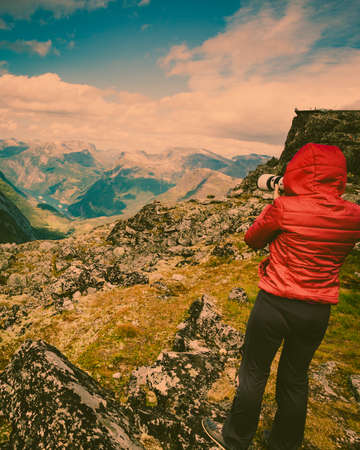 Female tourist taking photo with camera, enjoying Geirangerfjord and mountains landscape from Dalsnibba area. Geiranger Skywalk viewing platform in the distance. Norway. Banco de Imagens