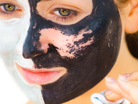 Woman with clay carbo black mask on one half face and white mud on second half. Girl removing cosmetic scrab with cotton swab. Female taking care of oily complexion. Skincare. Reklamní fotografie