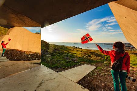 Tourist woman with norwegian flag enjoying sea coast view from Bukkekjerka rest stop area on Andoya island, Vesteralen archipelago, Norway. Фото со стока