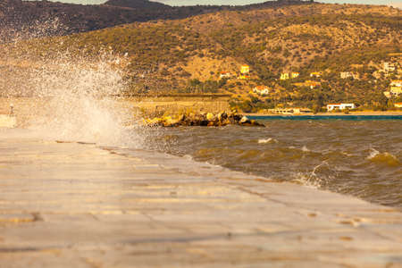 Sea water splashing on the edges of jetty pier reservoir wall in coastline town Greece. Stockfoto