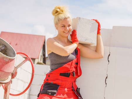 Strong pretty woman working on construction site, building house, installing gray airbricks. Industrial work concept.
