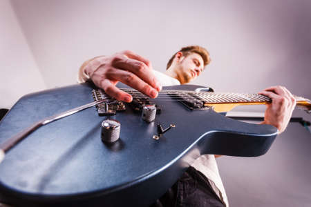 Young bearded man with electric guitar. Adult person is holding instrument and playing. Hobby, music concept, on grey Stock Photo - 129806104