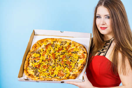 People, italian cuisine concept. Young woman holding hot fresh big pizza in box, on blue. Delicious fast food meal. Delivery service. Standard-Bild - 129806043
