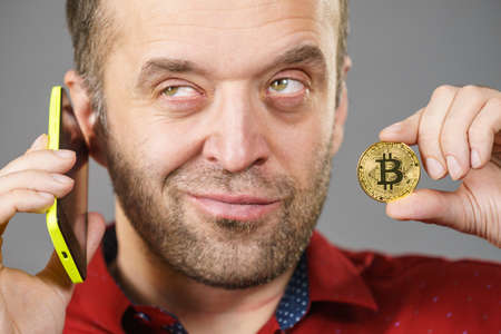 Man holding phone and crypto currency symbol. Adult guy using his smartphone calling to somebody having bitcoin in hand talking about business. Stockfoto