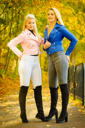 Two friends women wearing fashionable outfit. Female having navy bue pink leather jacket, jeans and high ankle black boots. Imagens