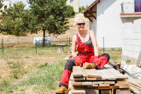 Woman in dungarees relaxing after hard work on construction site. Young female lying outdoor taking a break Stock fotó
