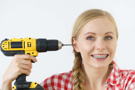 Funny cheerful woman pointing at her head or ear using drill. Crazy working female.
