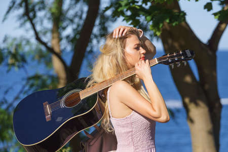 Hippie looking young adult woman wearing gypsy outfit having acoustic guitar. Female playing music in park. 스톡 콘텐츠