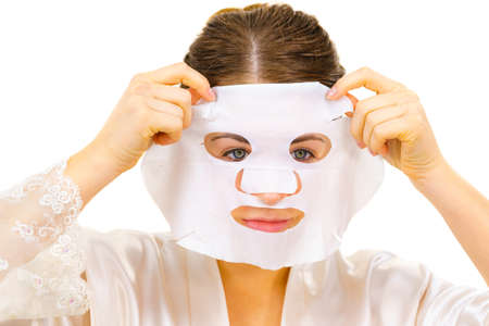 Woman applying sheet mask on her face, on white. Girl taking care of skin complexion. Beauty treatment. Skincare. 스톡 콘텐츠 - 129961298