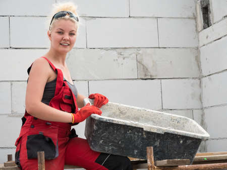 Woman wearing workwear working on construction site. Mixing cement in bowl preparing mortar. Partially built new home early stage. Industry. Reklamní fotografie