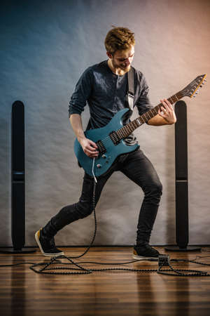 Young bearded man with electric guitar. Adult person in full length is holding instrument and playing. Hobby, music concept, on grey Stockfoto - 129961698