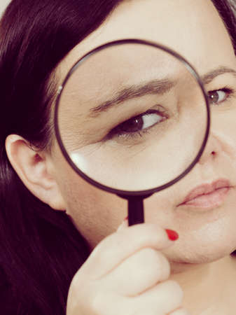 Adult woman holding magnifying glass investigating something and looking closely, trying to find solution.