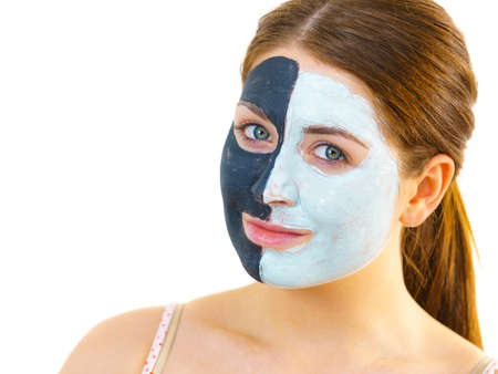 Woman with clay carbo black mask on half face and white mud on second half. Girl taking care of oily complexion. Beauty procedures. Skincare.