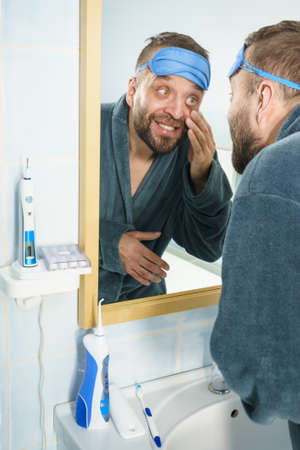 Funny adult man wearing eyemask on forhead having troubles with waking up. Standing in front of mirror looking at his dark circles under eyes, being tired and sleepy. 版權商用圖片