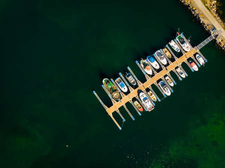 Aerial top down view. Marina dock basin with moorings and supplies for yachts and small fishing boats.
