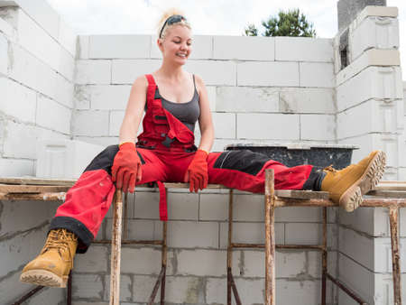 Smiling woman wearing workwear working on construction site. Partially built new home early stage. Industry.