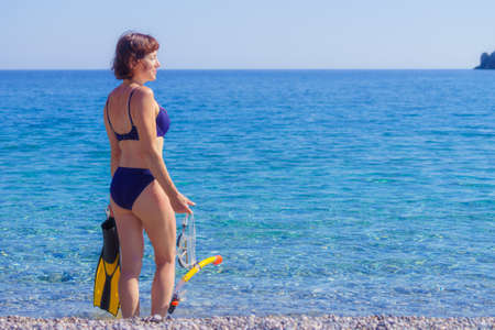 Mature female with snorkel equipment flippers and snorkeling mask tube on beach sea shore. Summer vacation swimming fun concept. Imagens