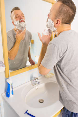 Man applying shaving foam cream on his face, standing in bathroom, looking at mirror, preparing to shave his face beard. Skincare 스톡 콘텐츠