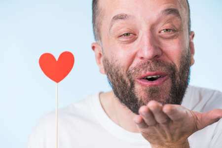 Adult man being in love holding small red shape heart on stick. Romance, flirting, Valentines Day concept. Фото со стока