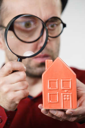 Funny looking adult man examining red model home using a magnifying glass, house inspection and real estate concept
