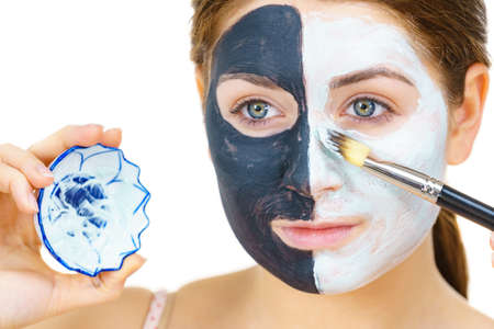 Woman with clay carbo black mask on half face applying white mud to clean skin. Girl taking care of oily complexion. Beauty procedures. Skincare. 스톡 콘텐츠