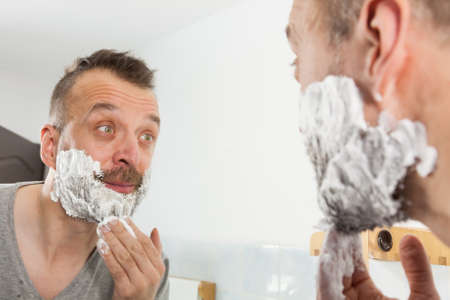 Man preparing his facial hair before trimming his beard, applying shaving cream foam mousse. Male beauty treatment concept.