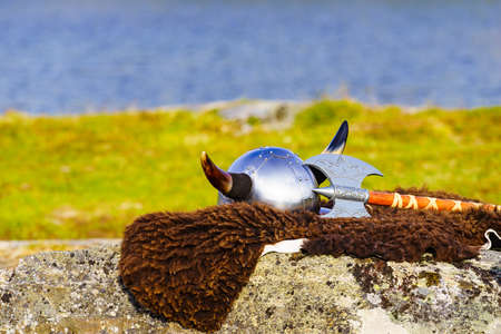 Equipment of viking or barbarian warrior outdoor on nature. Viking helmet with axe on brown fur of the animal in Norway. Tourism and traveling concept