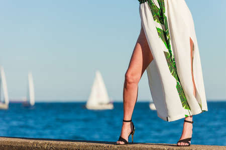 Woman legs wearing fashionable dress and high heels summer shoes. Female walking on sea coast. Yachts in the background Stok Fotoğraf - 130023892