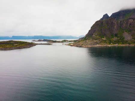 Sea landscape with islets among the waters of fjord Vjestfjord, Lofoten islands, Henningsvaer region, Norway. Hazy day, overcast weather. Banco de Imagens
