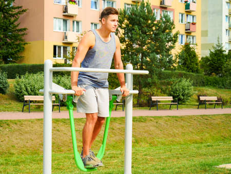 Young man working out in outdoor gym. Sporty guy doing legs exercises on street simulators. Staying fit and healthy. Stockfoto