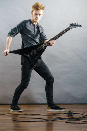 Man being passionate about his music hobby, playing electric guitar emotionally. Stock Photo