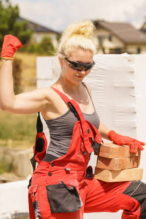Strong pretty woman working on construction site, building house, installing bricks. Industrial work concept.