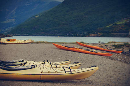 Kayaks on fjord shore in norwegian tourist destination Flam village. Travel, holidays and active lifestyle.