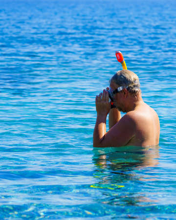 Man diver with snorkel equipment snorkeling mask tube in ocean water. Summer vacation swimming fun concept.