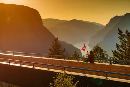 Tourist woman with norwegian flag enjoying fjord Aurlandsfjord view from Stegastein viewing point. National tourist route Aurlandsfjellet, Norway Stock Photo