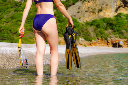 Unrecognizable mature female with snorkel equipment flippers and snorkeling mask tube on beach sea shore. Summer vacation swimming fun concept. Фото со стока