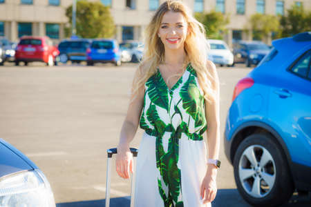 Beautiful fashion model woman arriving at the airport with suitcase on wheels standing on parking.