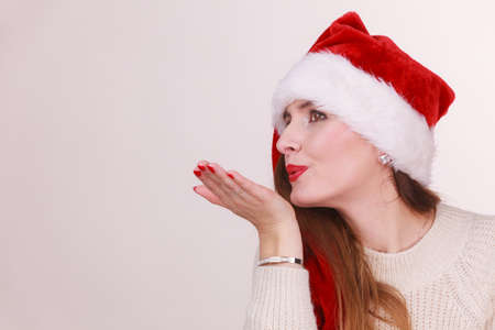 Christmas girl blowing a kiss. Young lady wearing santa claus cap. Celebration holiday happiness concept.