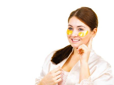 Woman applying golden collagen patches under eyes, on white. Mask removing wrinkles, dark circles. Girl taking care of delicate skin around eye. Beauty treatment. Reklamní fotografie
