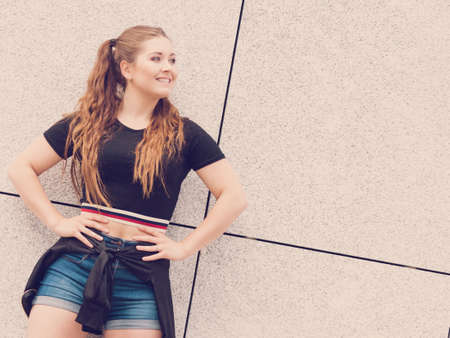Young teenage woman wearing denim shorts and black crop top. Female presenting fashionable summer outfit.