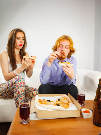 Man and woman spending time together. Couple or friends eating delicious cheesy pizza. Banco de Imagens