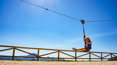 Adult freedom woman tourist having fun on zipline, descend on rope, cable aerial ropeslide. Mountains rest place in Spain Alicante region. Costa Blanca holiday. Banco de Imagens