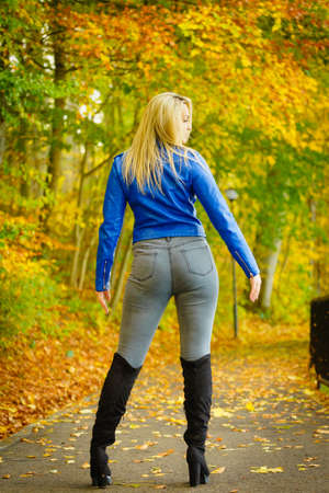 Sinnliche Frau, die modisches Outfit trägt. Frau mit dunkelblauer Lederjacke, Jeans und schwarzen Wildlederstiefeln mit hohem Knie, die im Park spazieren gehen.
