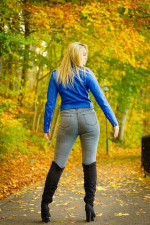 Zmysłowa kobieta nosi modny strój. Kobieta mająca granatową skórzaną kurtkę, dżinsy i zamszowe czarne buty do kolan spaceru w parku.
