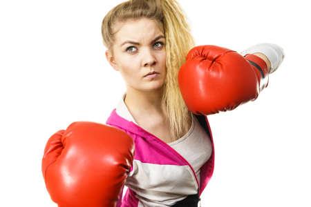 Sportiva donna sicura di sé che indossa guanti boxe rossi, combattimenti. Studio girato su sfondo bianco.