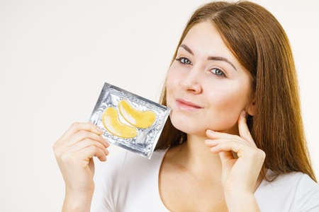 Young woman ready to applying golden collagen patches under eyes. Mask removing wrinkles and dark circles. Girl taking care of delicate skin around eye. Beauty treatment. Skincare.